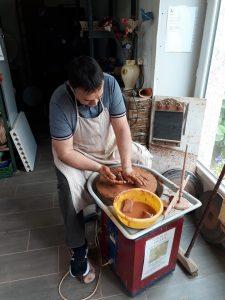 un éleve de mon cours de poterie essaye le tour de potier